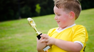 Young soccer player in uniform with his new trophy;